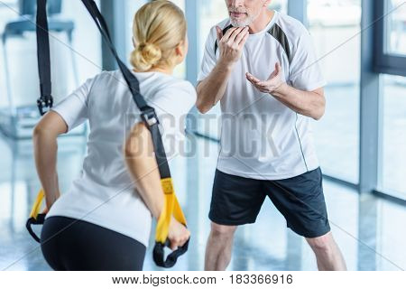 Sportswoman And Senior Trainer Training With Resistance Band In Sports Center