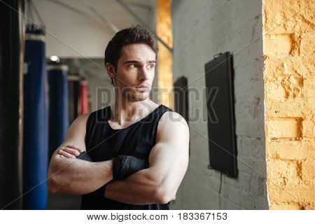 Calm boxer standing with crossed arms in gym and looking away