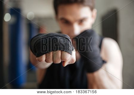 Close up  view of a young boxer doing exercise in gym. Focus on hand