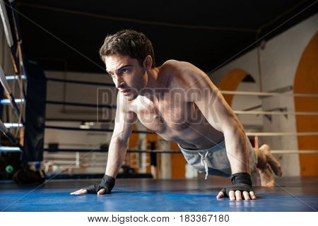 Side view of a cool boxer with naked torso doing push ups in boxing ring