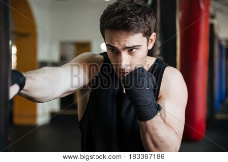Photo of young sportsman boxer make exercises with punching bag in gym and looking aside