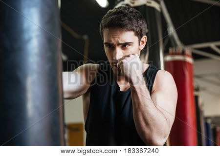 Attentive young boxer kicking punching bag in gym