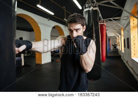 Concentrated boxer doing training in gym with punchbag