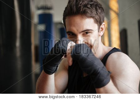 Close up  view of smiling boxer doing exercise in gym and looking at the camera