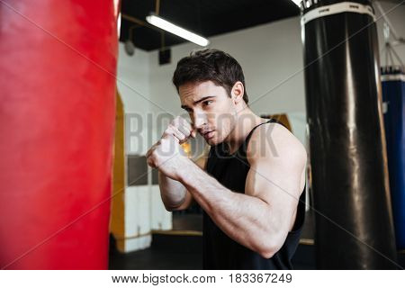Side view of boxer  training in gym with punchbag