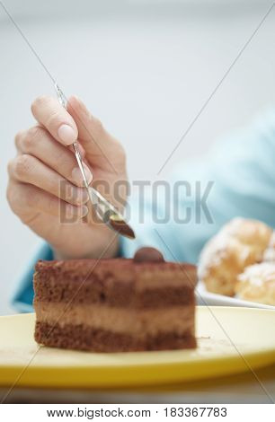 Hand of woman eating chocolate cake. Vertical photo