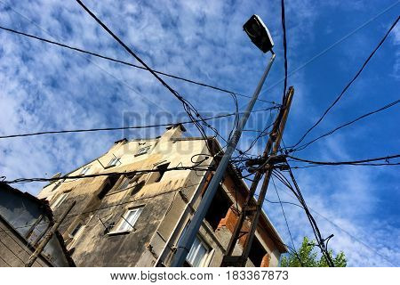 A lot of electric wires to a pole in the city on the background of blue sky and houses
