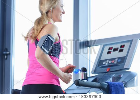 Low Angle View Of Sporty Blonde Woman Exercising On Treadmill In Gym