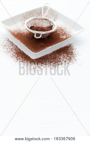 Metal sieve filled with cocoa powder on white square porcelain plate on white background with lots of copy space in the front. Backlit shallow depth of field and selective focus on the cocoa powder in the sieve.