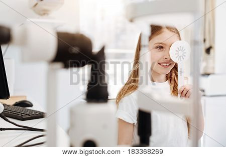 I can see everything. Stunning diligent young lady holding a special tool covering one of her eyes while reading letters from special test chart