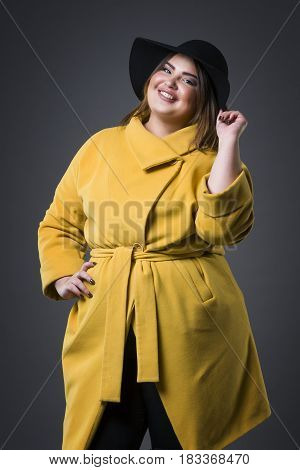 Plus size fashion model in yellow coat and black hat fat woman on gray studio background overweight female body