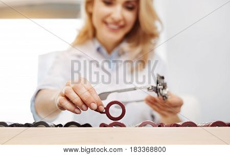 Ordering tools. Lovely positive professional optician creating a set of trial spectacles while helping her patient choosing appropriate glasses