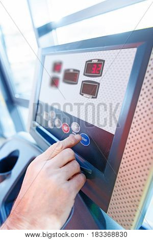 Close-up Partial View Of Hand And Interface Of Fitness Machine In Gym