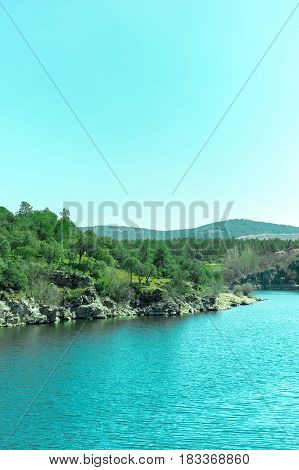 The river Lozoya in the community of Madrid, near the town of Buitrago, toned photo. This river is a source of drinking water in Madrid