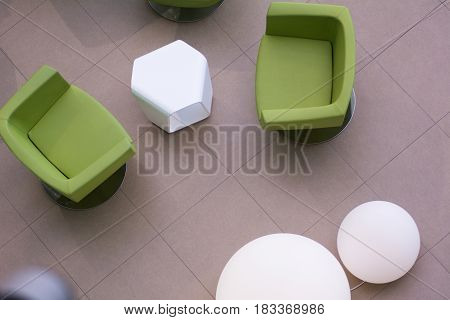 Top View Of Green Leather Chairs And Round White Lamps