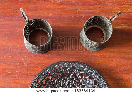 Two Old Metal Cup Holder And Openwork Cast-iron Plate. Old House And Old Table.