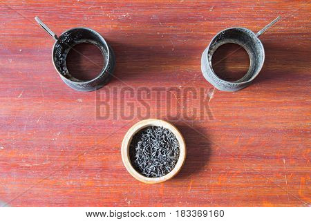 Two Old Metal Cup Holder And Tea In  Wooden Bowl. Old Wooden Table.