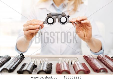 These are for you. Prominent talented famous specialist asking her patient wearing special glasses for indicating the most suitable lenses