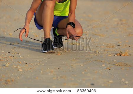 young fitness woman runner tying shoelace before run on beach