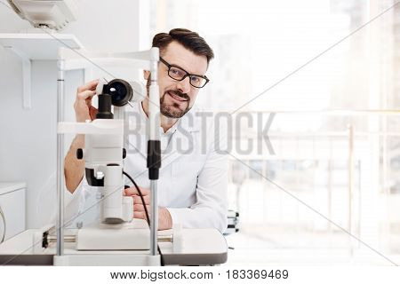 Would you sit here, please. Capable talented excellent doctor setting up the equipment for examining his patients eyes and establishing the diagnosis