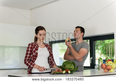 Young handsome couple in the kitchen  beautiful woman preparing a salad while the man eating an apple