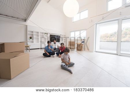 portrait of happy young boys with their dad sitting on the floor in a new modern home