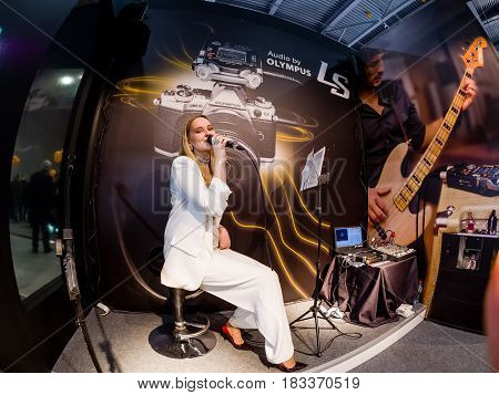 MOSCOW, RUSSIA - APRIL 21, 2017: Unidentified singer demonstrates LS-100 stereo audio recorder at Art Space booth of Olympus company at PhotoForum 2017 trade show in Moscow, Russia on April 21, 2017.