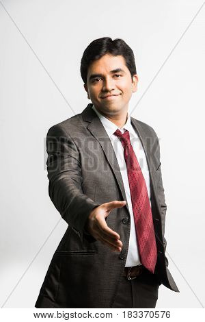 indian young businessman offering handshake or approaching for hand shake / shake hand, isolated over white background
