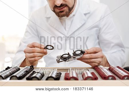 Productive work. Great distinguished wise doctor creating a set of trial spectacles while choosing needed details from special spectacle case