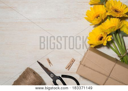 Wrapping flowers gift over wooden background. Top view with copy space