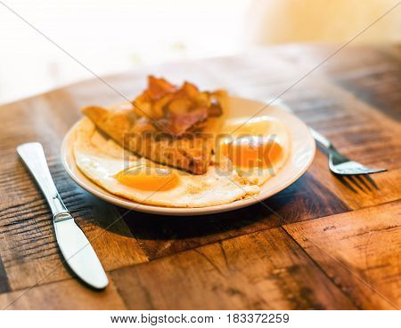 American breakfast with fried egg, becon and bread