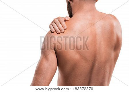Man with pain in shoulder against white studio background