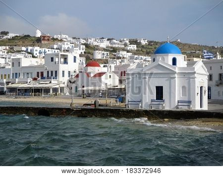 White church with blue dome and white church with red dome at the waterfront of Mykonos Old Port, Mykonos Island, Greece