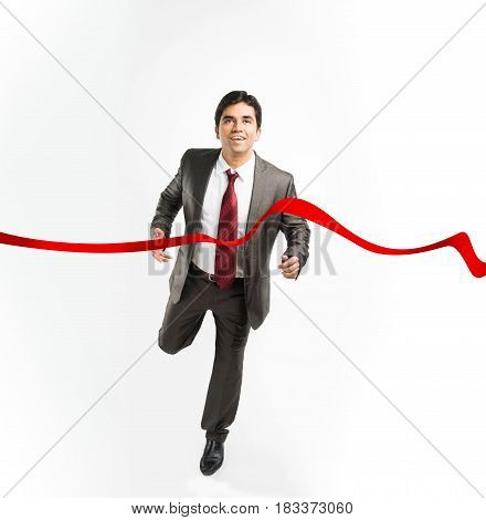 businessman and success concept - indian businessman successfully completing running marathon or race at first positing while touching red finishing ribbon, wearing complete corporate dress over white