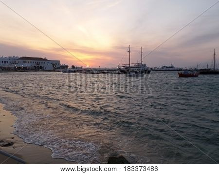 Sunset in Mykonos town with many boats at the Old Port, Mykonos Island, Greece