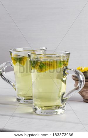 Two cups of herbal tea with coltsfoot (or Tussilago) flowers