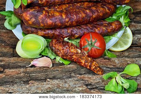 Tasty smoked sausages with seasoned salad ready for consumption.