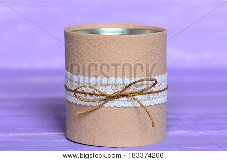 Recycled can isolated on wooden background. Tin can decorated with felt and lace. Easy way to make crafts for home. Recycling tin can into organizer or planter for kitchen or vase. Closeup