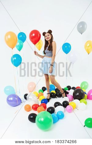 Charming girl with cool hairstyle holding red helium balloon, looking straight on white background