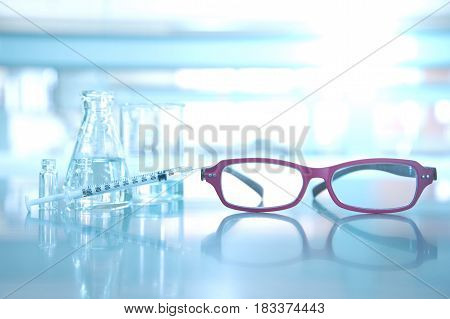 red glasses with syringe flask vial beaker in medical science laboratory bckground