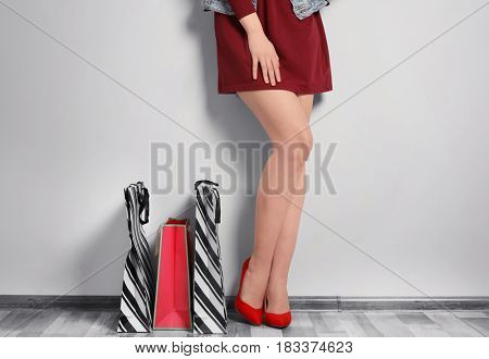 Beautiful young woman with paper bags indoors