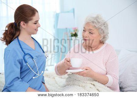 Nurse talking with elderly woman in light room