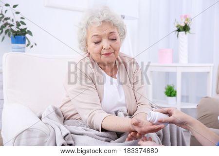 Elderly woman taking pills in light room