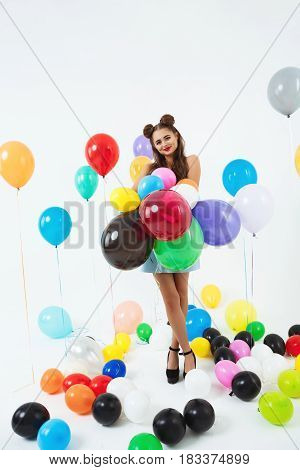 Nice teen girl in pin-up clothes holding bunch of balloons looking srtraight at camera
