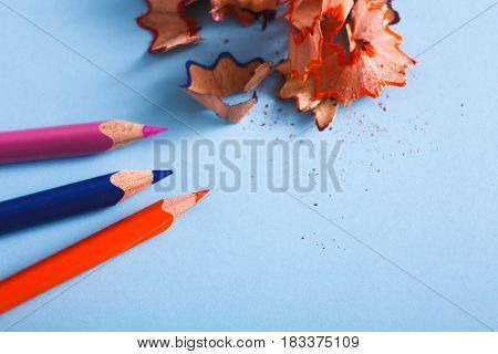 Stationary supplies - wooden color pencil shavings on blue background, flat lay, copy space, close-up