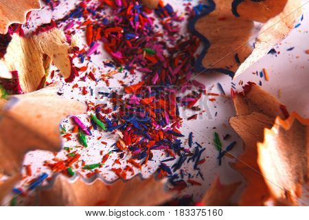 Wooden colorful pencil sharpening shavings closeup as abstract background. Art and education