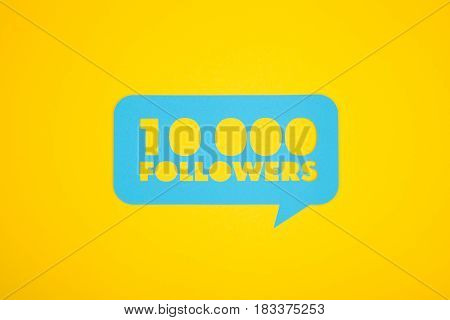 The 10 000 followers text cut out in a blue cardboard bubble.