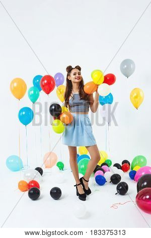 Pretty young woman in stylish outfit posing with helium balloons at bright party. Having fun