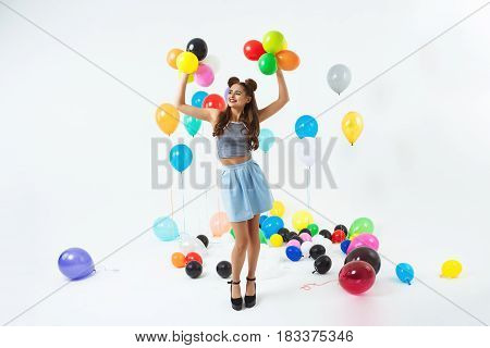 Girl in hipster clothing holding hands up with little colourful balloons posing on white background
