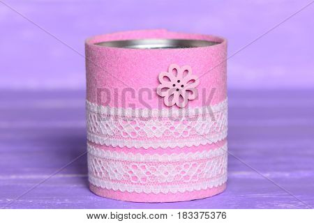 Recycled can isolated on wood background. Tin can decorated with felt, lace and flower button. Inexpensive way to make craft projects for home. Recycling tin can into organizer or planter for kitchen